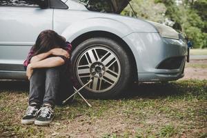 giovane donna hipster con una gomma a terra sulla sua auto