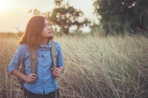 immagine tono vintage di una donna giovane e bella hipster con zaino in un prato foto