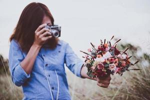 primo piano della mano della donna giovane hipster che tiene la retro macchina fotografica e la foto della ripresa del mazzo rosso
