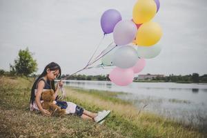 bambina con un orsacchiotto e palloncini sul campo di prato foto
