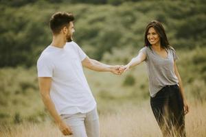 felice giovane coppia innamorata camminando attraverso il campo in erba