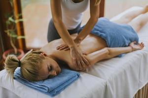 bella giovane donna sdraiata e con massaggio alla spalla nel salone spa durante la stagione invernale foto