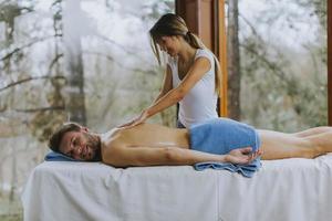 bel giovane uomo sdraiato e con massaggio alla schiena nel salone spa durante la stagione invernale foto