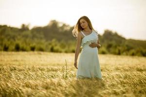 giovane donna incinta nel campo foto