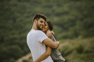 felice giovane coppia innamorata al campo in erba foto