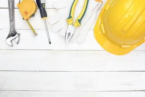 laici piatta di strumenti di costruzione su legno bianco con copia spazio sottostante foto