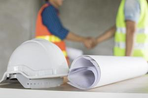 casco e stampe blu su un tavolo con il team di ingegneri che agitano le mani in background foto