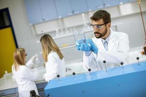 giovani ricercatori che lavorano con liquido blu in vetro da laboratorio foto