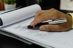 un uomo d'affari che tiene la penna sui documenti aziendali foto