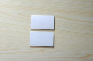 un mockup di carta bianca per biglietti da visita su un tavolo di legno foto