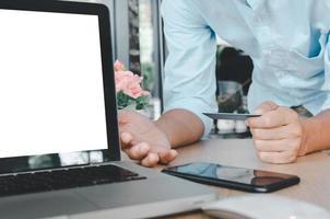 uomo d'affari in possesso di una carta di credito con il computer portatile sul tavolo. acquista online ed effettua operazioni di pagamento concetto aziendale