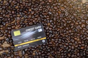 una carta di credito posta sui chicchi di caffè foto