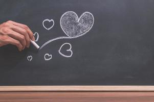 mano che disegna un doodle di cuore foto