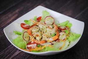 insalata con lattuga, ravanelli, pomodorini e gamberetti in un piatto bianco sulla tavola di legno foto