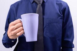 un uomo con in mano una tazza di caffè foto