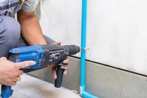 lavoratore utilizzando un utensile elettrico di perforazione sul sito in costruzione foto