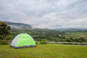 tenda che si affaccia su un nuvoloso paesaggio montano foto