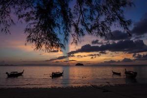 silhouette di barche sull'oceano al tramonto foto