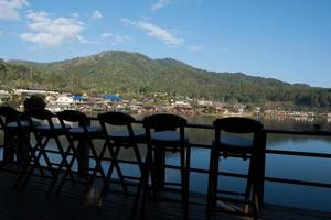 sedie di fronte a una vista di un villaggio e acqua