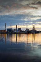 riflessione della raffineria di petrolio sull'acqua foto