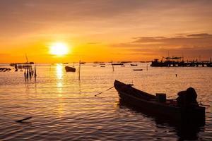 barche in acqua con un tramonto arancione