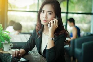 donna asiatica è al telefono in un caffè