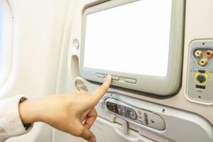 donna che punta il dito sullo schermo lcd bianco vuoto su un aeroplano