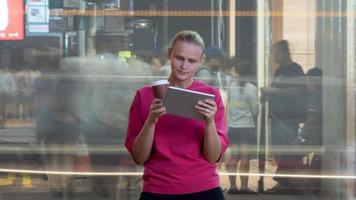 hong kong, 2020 - donna con un tablet vicino a una strada affollata