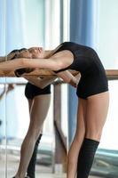 giovane ballerina che si estende alla sbarra