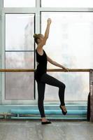 giovane ballerina che si esercita alla sbarra in studio