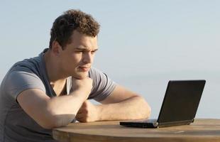 uomo che utilizza un computer portatile all'esterno foto
