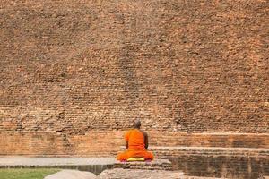 monaci buddisti seduti davanti al vecchio stupa nella città di kushiingar, india