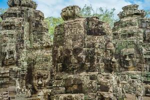 antiche facce di pietra del tempio bayon, angkor wat, siam reap, cambogia