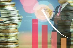 grafici e monete si sovrappongono con l'uomo d'affari in questa tuta foto