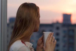 donna che beve il tè guardando un tramonto