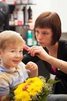 giovane ragazzo che ottiene taglio di capelli da uno stilista foto