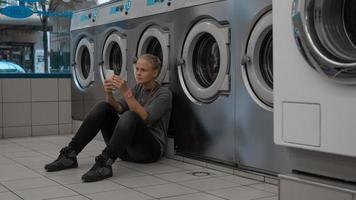 donna sul suo telefono in una lavanderia a gettoni foto