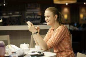 donna sul suo telefono in un ristorante foto