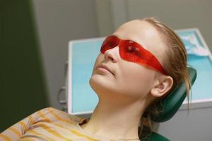 donna in occhiali di sicurezza rossi in uno studio dentistico foto