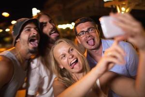 giovani che si divertono prendendo un selfie di notte foto