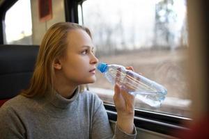 donna che beve acqua e guardando fuori dal finestrino del treno