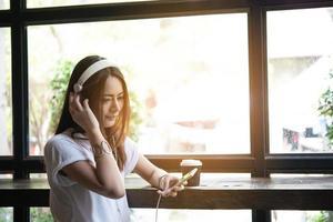 giovane donna che ascolta la musica in cuffia con sfondo davanzale.