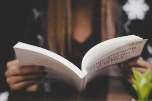 primo piano della donna che tiene un libro