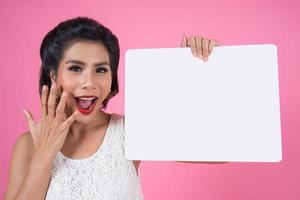 ritratto di una donna alla moda che mostra uno striscione bianco foto