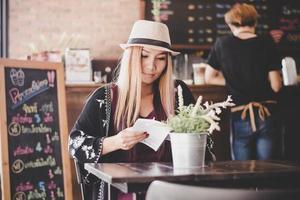 donna d'affari felice leggendo il libro mentre vi rilassate al caffè