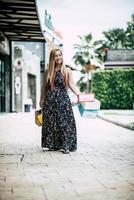 ritratto di una giovane donna felice con le borse della spesa a piedi per la strada