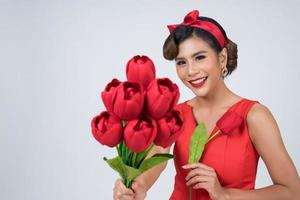ritratto di una bella donna con bouquet di fiori di tulipano rosso foto