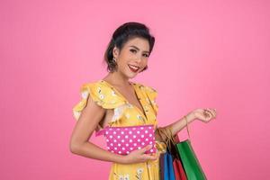 giovane donna alla moda che tiene un portafoglio con contanti e borse della spesa foto
