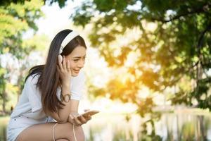 ritratto di una ragazza sorridente con le cuffie che ascolta la musica in natura foto