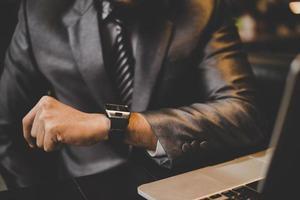 primo piano dell'uomo d'affari guardando l'orologio foto
